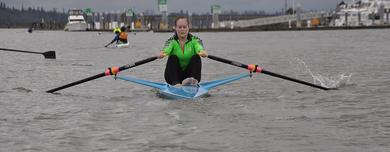 Woman focuses as she rows away fast
