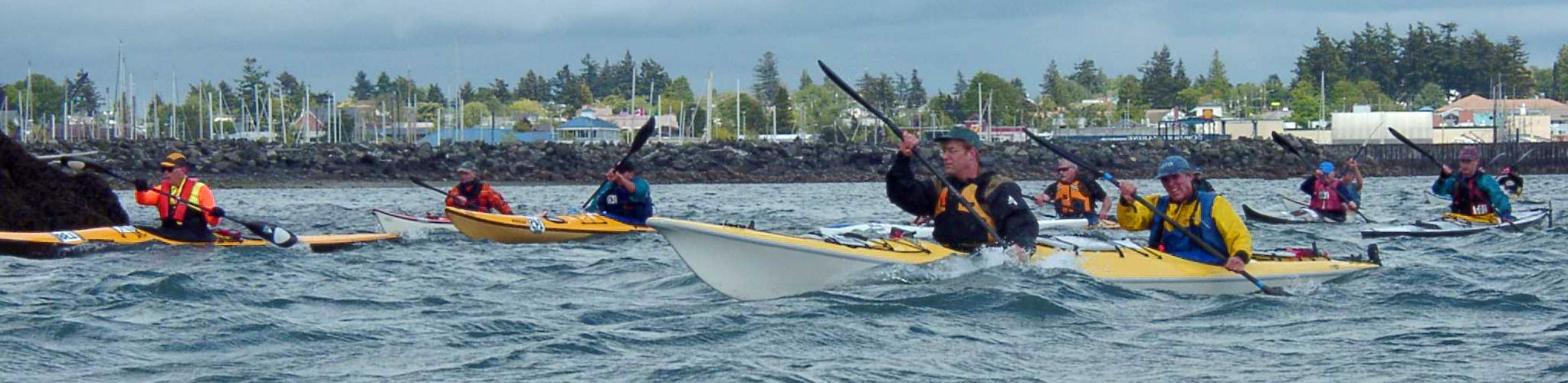Two men in a double kayak strain to push ahead of the pack