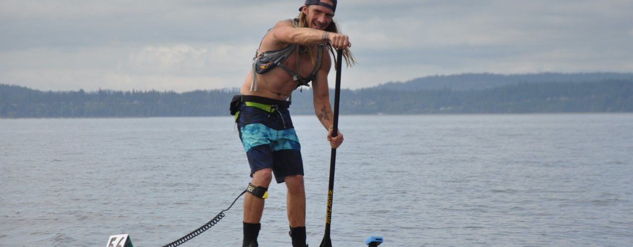 Strong SUP racer smiles as he pauses from paddling