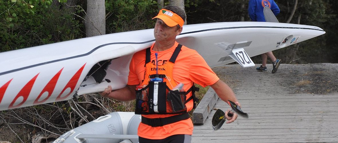 """Paddler says, """"Why not?!"""" as he carries surfski to the race start"""