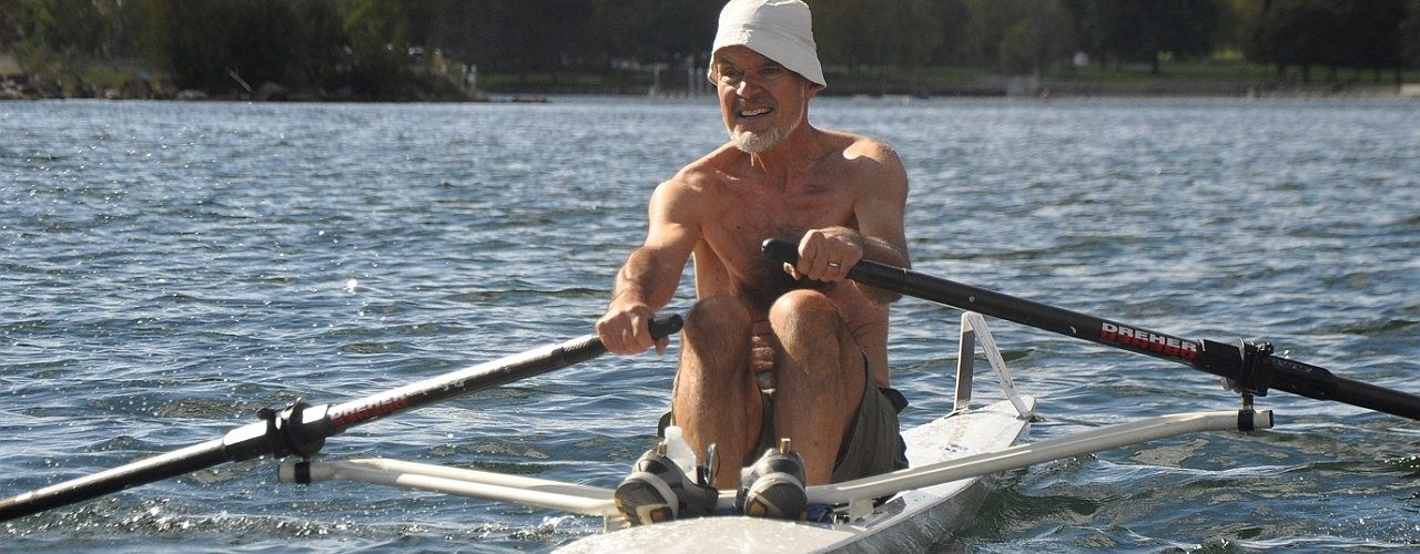 Rower in fishing hat smiles in the sun