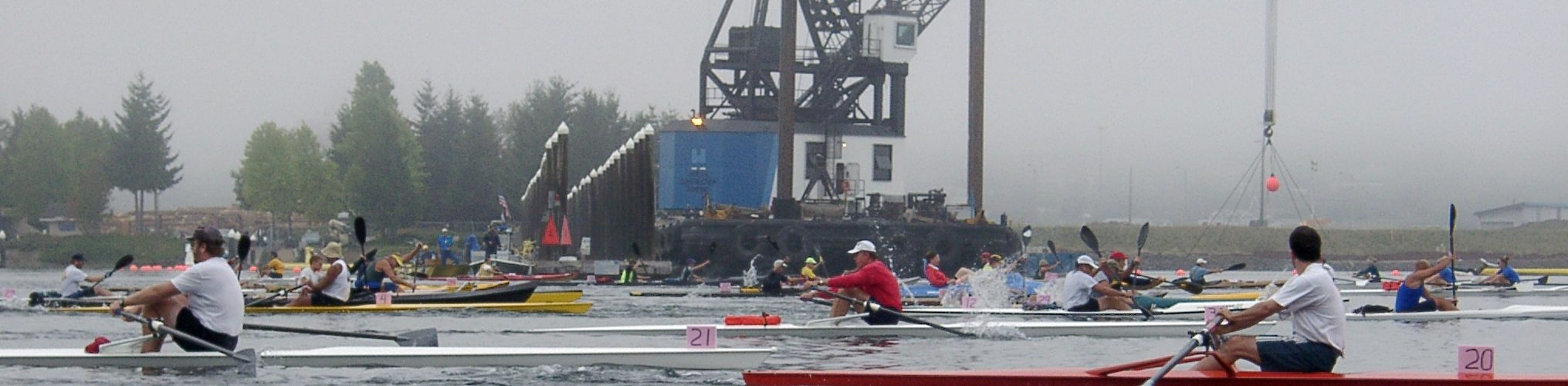Large group of rowers and paddlers race past industrial crane