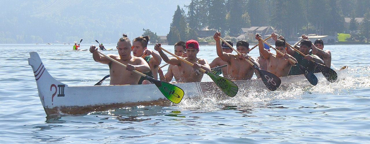 10-man war canoe with blades splashing