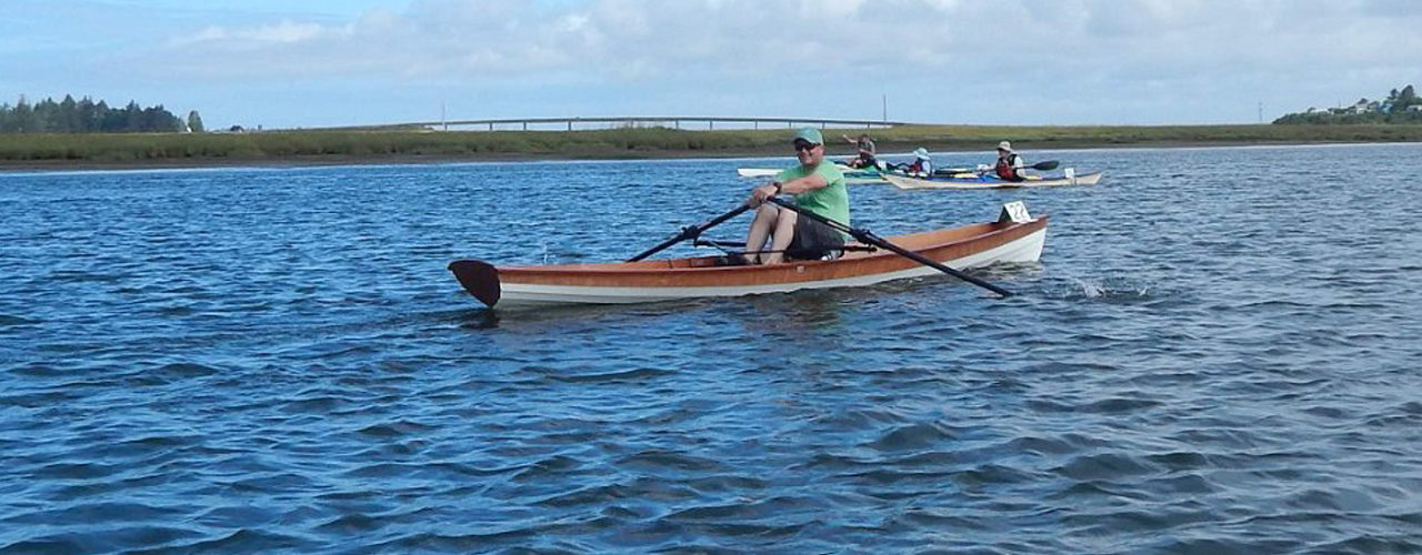 Man smiles as he rows past in his wooden wherry on a sunny day