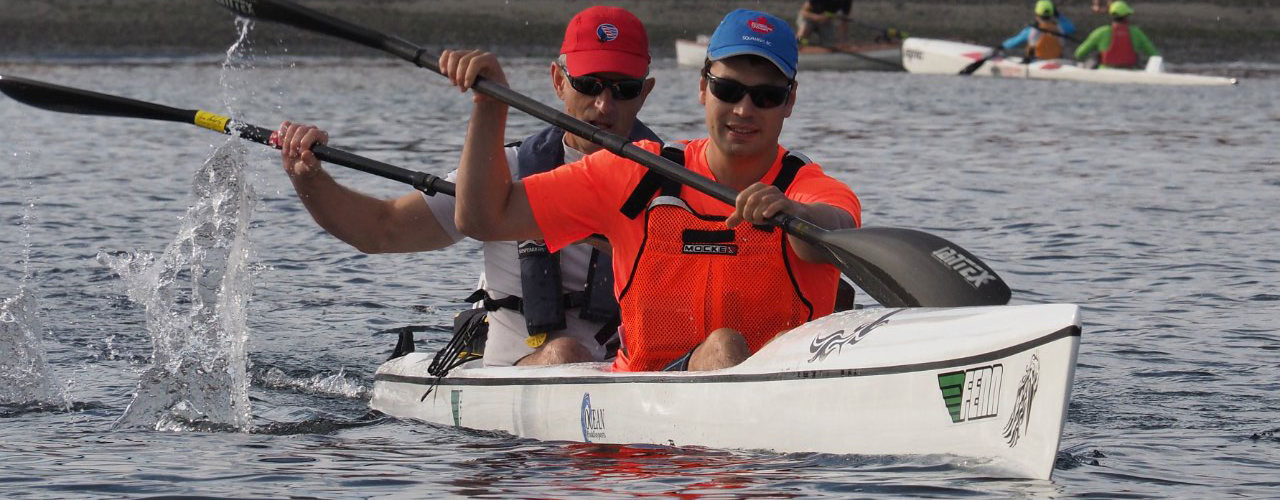 Two men in a surfski smile as they paddle toward us