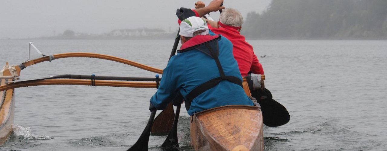 Heikkila's wooden OC 6 paddles away in dark waves