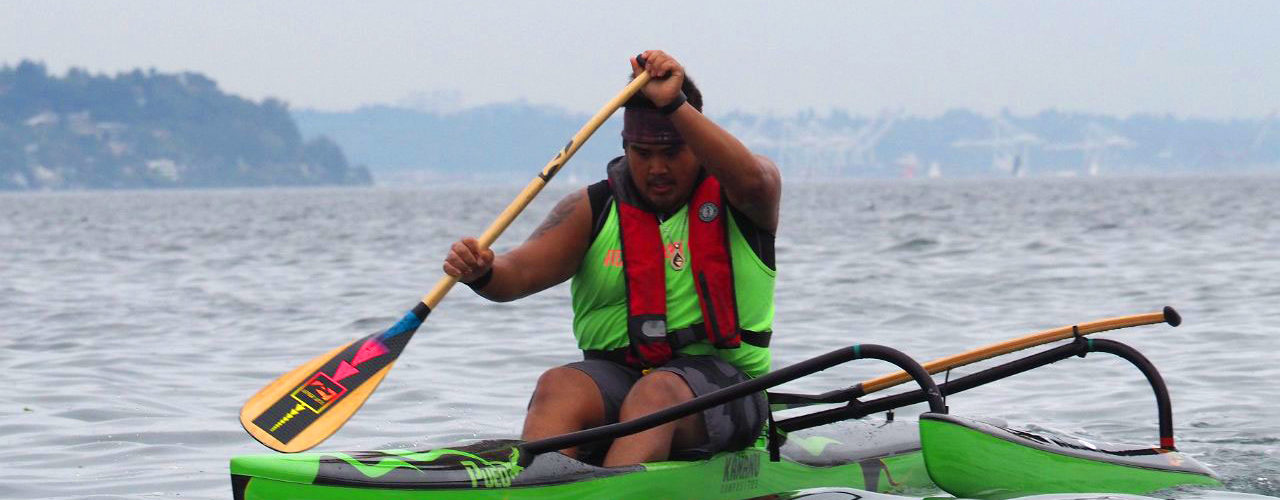 Young man paddles his green Outrigger Canoe
