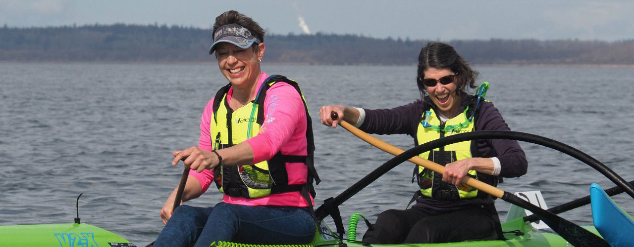 Two women laugh as they paddle their OC2