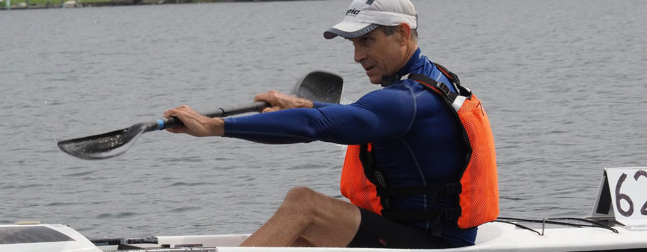 Man with razor-sharp focus paddles his surfski with precision