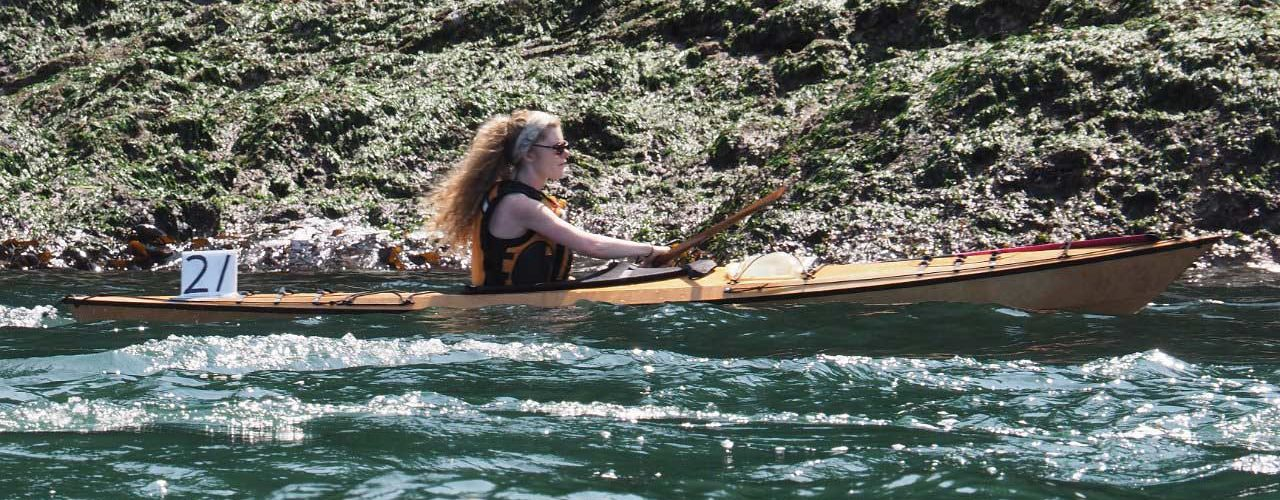 Woman's red hair flows as she navigates green waters in a wooden kayak